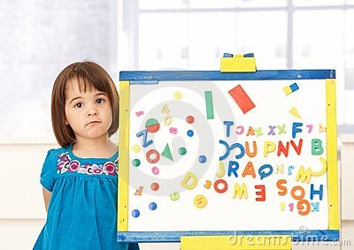 Sweet small girl standing at drawing board
