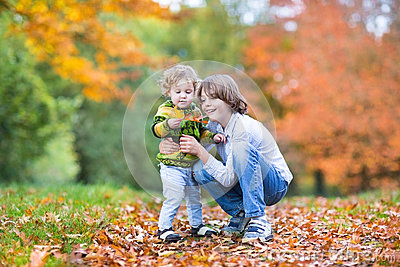 Sweet toddler girl and her brother in autumn park