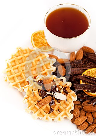 Sweet waffles with chocolate, nuts and a cup of te