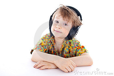 Sweet young boy listening to music on headphones