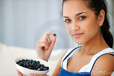 Sweet young woman eating blackberries at home