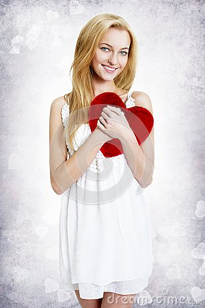 Sweet young woman holding red heart pillow