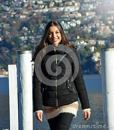 Free Sweet Young Woman With Winter Clothes Walking On Pier Gangway Of Lake Lugano With Mountains On The Background And Flare Sun Light, Stock Image - 106082841