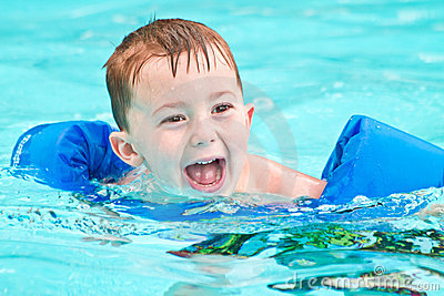 Swimming boy in pool with big smile