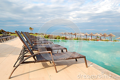 Swimming pool by beach at the modern luxury hotel