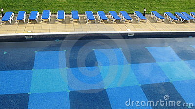 Swimming pool and row of deck chairs