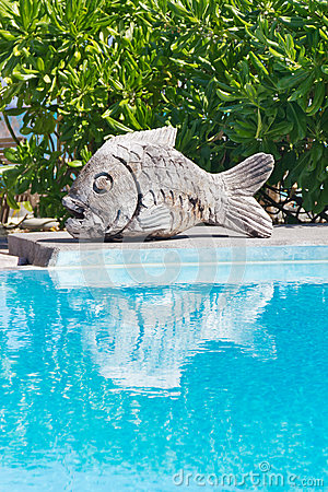 Swimming pool with wooden carved fish sculpture