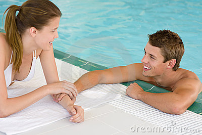 Swimming pool - young loving couple hold hands