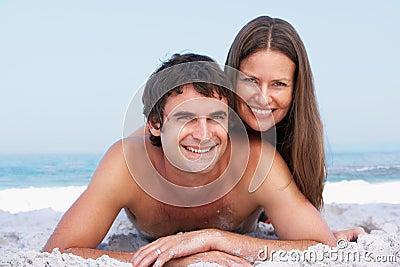 Νέα χαλάρωση ζεύγους στην παραλία που φορά Swimwear
