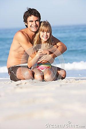 Swimwear desgastando do pai e da filha que senta-se para baixo