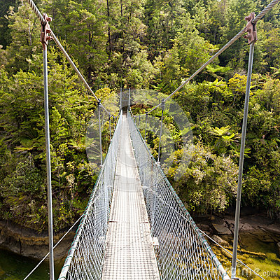 Free Swing Bridge Over Green Jungle River New Zealand Royalty Free Stock Image - 63194636