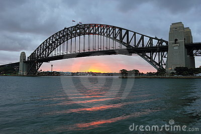 Sydney Harbour Bridge at sunset by clouded sky