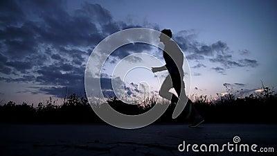 Sylwetka mężczyzna bieg na drodze przy zmierzchem zdjęcie wideo