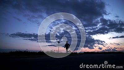 Sylwetka mężczyzna bieg na drodze przy zmierzchem zbiory