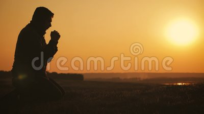 Sylwetka m?odego cz?owieka ono modli si? outside przy pi?knym zmierzchem Samiec pyta dla pomocy znalezienia utulenia w wiarze, po zbiory
