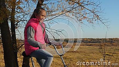 Szczęśliwa dziewczyna w różowej kurtce jedzie bicykl w jesień parku ręki dziewczyna trzymają przegiętego handlebar zdjęcie wideo