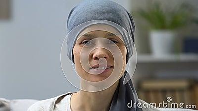 Szczęśliwa nowotworu ocalały kobieta ono uśmiecha się przy kamerą, darowaniem i nadzieją dla wyzdrowienia, zbiory