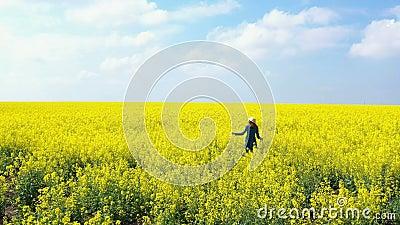 Szczęśliwa, piękna dziewczyna, bawiąca się na kwitnącym polu rzepaku zdjęcie wideo