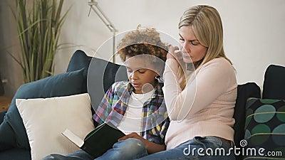 Szczęśliwa rodzina czyta razem historię z książki, w której trzymają małego chłopca zbiory