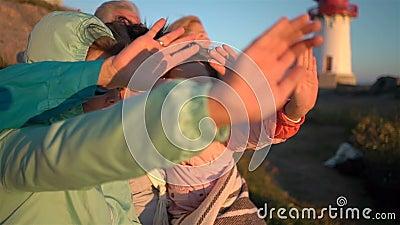 Szczęśliwa rodzina podziwia wschód słońca na skalistym Północnym brzeg morze z starą latarnią morską lub zmierzch zbiory wideo