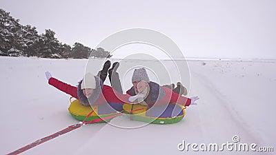 Szczęśliwe dzieci śpiące na śnieżnej drodze zimą i śmiejące się Gry na platformę Fun Tubing Podróże i wakacje na Boże Narodzenie zbiory wideo