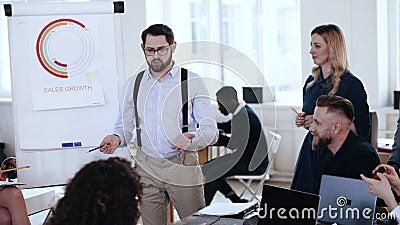 Szczęśliwego fachowego młodego uśmiechniętego biznesmena brainstorm wiodąca skoczna dyskusja z różnorodną drużyną przy biurowym s zdjęcie wideo