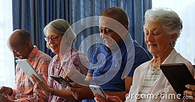 Szczęśliwi starsi przyjaciele używa cyfrową pastylkę w żywym pokoju 4k zbiory