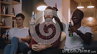 Szczęśliwi, wieloetniczni młodzi mężczyźni oglądają mecz w telewizji, piją drinki, uśmiechają się i rozmawiają z rozrywką w zwoln zdjęcie wideo