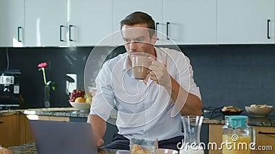 Szczęśliwy biznesowego mężczyzny dopatrywania wideo w dużej kuchni Pesron dostaje szokującą wiadomość zbiory wideo
