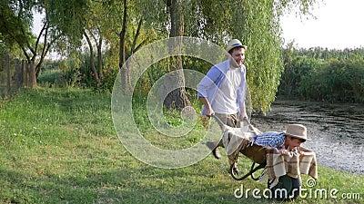 Szczęśliwy dzieciństwo, najlepszy ojczulek zabawa jechać jego dziecko chłopiec w wheelbarrow przy wsią zdjęcie wideo