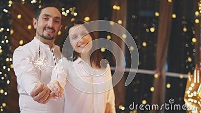 Szczęśliwy mężczyzna i kobieta z bengalskimi światłami, patrzący na siebie czule i uśmiechający się, mając przyjemność w Nowym Ro zbiory