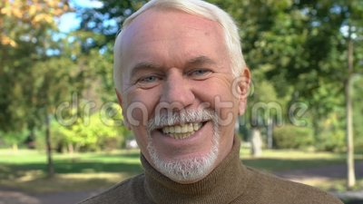 Szczęśliwy mężczyzna uśmiechający się do kamery, pozytywny emeryt, opieka dentystyczna, przyjemność zbiory wideo
