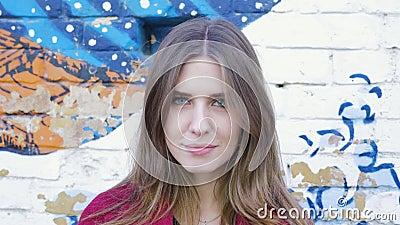 Szczęśliwy młodej kobiety pozyci przód ściana z cegieł, patrzeje kamerę Młoda atrakcyjna kobieta patrzeje kamerę na zbiory