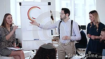 Szczęśliwy młody Kaukaski biznesmen daje rozmowie przy sprzedaży flipchart, aktywny drużynowa dyskusja przy nowożytnym biurowym k zbiory