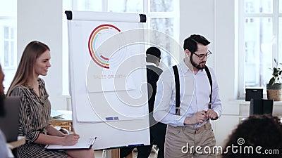 Szczęśliwy młody uśmiechnięty CEO szefa mężczyzna daje seminaryjnej rozmowie przy flipchart, wiodąca drużynowa dyskusja przy nowo zbiory