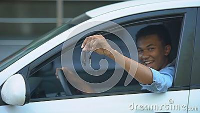 Szczęśliwy nastolatek pokazujący kluczyki do okna siedzącego na siedzeniu kierowcy nowego pojazdu zdjęcie wideo