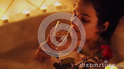 Szczęśliwy piękny młodej dziewczyny lying on the beach w łazience z pianą z różą w jej pić szampanie i ręce zbiory wideo