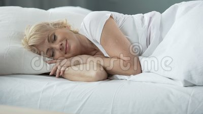 Szczęśliwy w średnim wieku żeński dosypianie w łóżku na ortopedycznej materac, zdrowie zdjęcie wideo