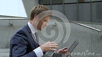 Szczęsliwy biznesmen używa laptop sprawdzać rynek papierów wartościowych, siedzi na schodkach outdoors zbiory wideo