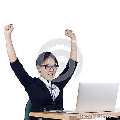 Szczęśliwa biznesowa kobieta pracuje na laptopie przy biurem