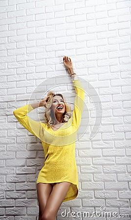 Szczęśliwa blondynki kobieta pozuje z toothy uśmiechem.