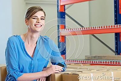 Szczęśliwy żeński pracownik ono uśmiecha się w magazynie