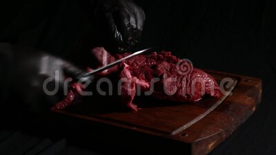 Szef kuchni przygotowuje mięso do pieczenia dłonie rzeźnika kroją kawałki mięsa nożem zbiory