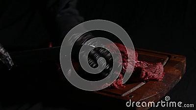 Szef kuchni przygotowuje mięso do pieczenia dłonie rzeźnika kroją kawałki mięsa nożem zbiory wideo