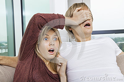 Täckande mans för chockad kvinna ögon, medan hålla ögonen på TV hemma