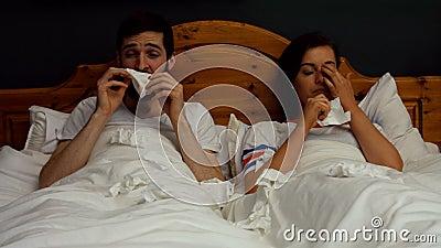 Täckande näsa för par, medan nysa på säng stock video