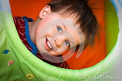Tät lycklig stående för pojke som ler upp