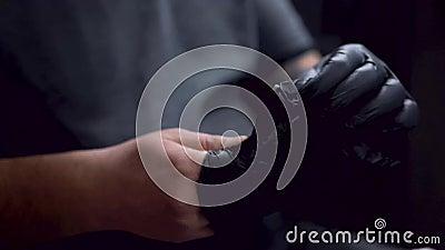 T?towierungsk?nstler tr?gt einen schwarzen Handschuh stock footage