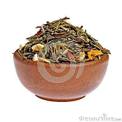 Té verde de la fruta seca en una taza de la arcilla