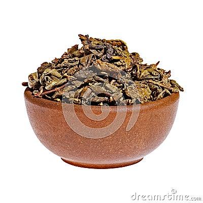 Té verde seco en una taza de la arcilla
